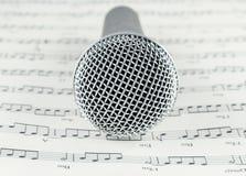 Mikrofon na Muzykalnych notatek papierze Zdjęcia Royalty Free