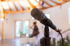 Mikrofon na prostym stojaku z rozmytą kobietą daje konferencji, zdjęcie stock