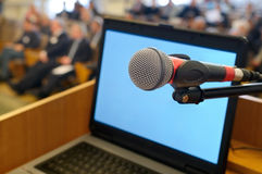 Mikrofon- och bärbar datorskärm på konferensen. arkivbild