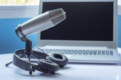 Mikrofon och hörlurar med solitt redigerande begrepp för bärbar dator Royaltyfri Foto