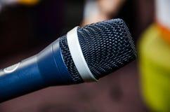 Mikrofon på abstrakt suddigt av anförande i seminariumrum eller talande ljus för konferenskorridor Arkivbilder