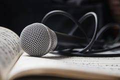 Mikrofon på arket av musik Royaltyfria Bilder