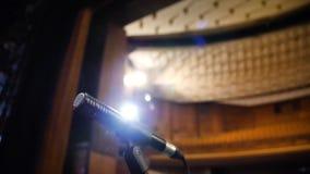 Mikrofon på etappen och tom korridor under repetitionen Mikrofon på etapp med etapp-ljus i bakgrunden Royaltyfri Bild