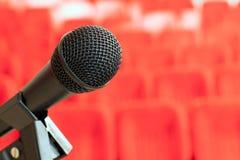 mikrofon på ställningen i en tom aula med röda stolar begrepp av utbildning, affärsmöten och konferenser royaltyfri fotografi