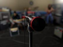 mikrofonen 3D och musikbandet framför Royaltyfri Foto