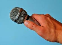 Mikrofonen räcker in royaltyfri foto