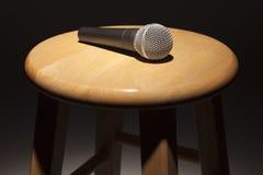 Mikrofonen som lägger på trä, pallr under strålkastare Arkivbilder