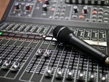 Mikrofonen vilar på en ljudsignal blandarekontrollant i kontrollrummet, kontrollen för solid blandare för levande musik och studi arkivfoto