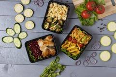 Mikrogräsplaner för lunchtid, klart mål att äta i matcontiners på den gråa tabellen, zucchiniskivor, suddig bakgrund fotografering för bildbyråer