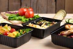 Mikrogräsplaner för lunchtid, klart mål att äta i matcontiners, zucchiniskivor, suddig bakgrund royaltyfri fotografi
