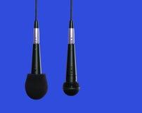 Mikrophone, die nebeneinander hängen Stockbild