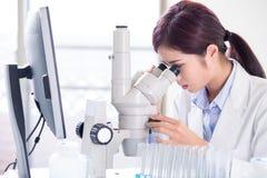 Mikroskop för kvinnaforskarebruk royaltyfria foton