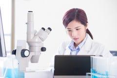 Mikroskop för kvinnaforskarebruk arkivfoton