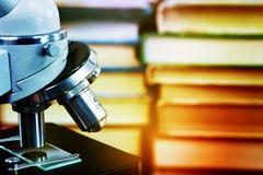 Mikroskop mot en bakgrund av böcker Royaltyfri Bild