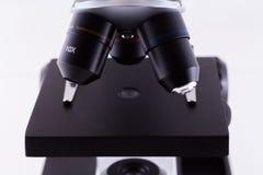 Mikroskop på vitbakgrund Arkivfoto