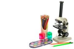 Mikroskop und anderer Schulbedarf lokalisiert auf weißem backgroun lizenzfreie stockbilder