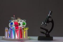 Mikroskop z chemiczną eksperyment tubką W laboratorium naukowym z popielatym tłem zdjęcie stock