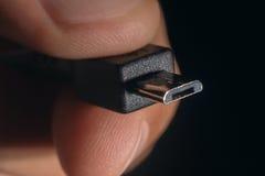 MikroUSB för handinnehavsvart kabel Mannens hand rymmer ett USB microkontaktdon royaltyfri fotografi