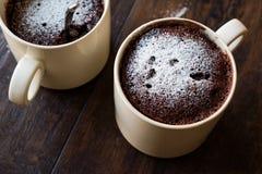 Mikrovåg Brownie Chocolate Mug Cake med pulversocker på mörk träyttersida Royaltyfria Foton