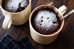 Mikrovåg Brownie Chocolate Mug Cake med pulversocker på mörk träyttersida Royaltyfria Bilder