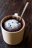 Mikrovåg Brownie Chocolate Mug Cake med pulversocker på mörk träyttersida Arkivbild