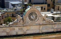 Milán, Italia - 21 de abril de 2012: El reloj con las esculturas en la fachada del edificio vista del tejado del Duomo Fotografía de archivo