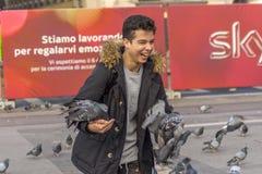 Milán, Italia 23-11-2017 Hombre joven feliz con las palomas en el cuadrado delante de Milan Cathedral Di Milán del Duomo imagen de archivo