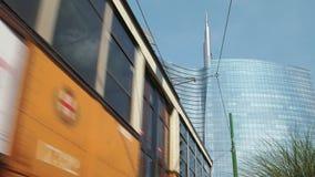 Milán, Italia - mayo de 2016: La torre de Unicredit, tiro bajo, tranvía pasa cerca almacen de metraje de vídeo