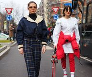 MILÃO - 25 DE FEVEREIRO DE 2018: Duas mulheres elegantes que andam na rua antes do desfile de moda de ARMANI Fotos de Stock Royalty Free