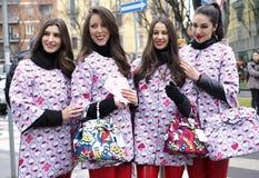 MILÃO - 25 DE FEVEREIRO DE 2018: Meninas da vaquinha que levantam para fotógrafo na rua antes do desfile de moda de ARMANI, duran Imagens de Stock