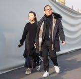 MILÃO - 14 DE JANEIRO: Pares asiáticos que andam na rua antes do desfile de moda DSQUARED2, durante Milan Fashion Week Imagens de Stock Royalty Free