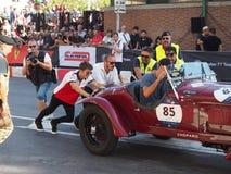 Milão, Itália - 29 de agosto de 2018: Charles Leclerc que ajuda a mover um carro após uma falha do começo foto de stock