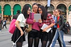 Milão, Itália - 19 de outubro de 2014: A menina que olha a tabuleta fez fotos e selfie fotos de stock royalty free