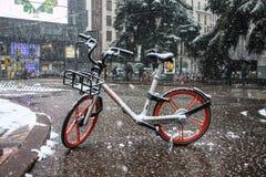 Milão, Itália, o 1º de março de 2018 Ruas de Milão na neve Vista na bicicleta alugado Fotos de Stock