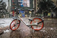 Milão, Itália, o 1º de março de 2018 Ruas de Milão na neve Vista na bicicleta alugado Foto de Stock