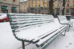 Milão, Itália, o 1º de março de 2018 Ruas de Milão na neve Vista no banco coberto na neve Imagem de Stock