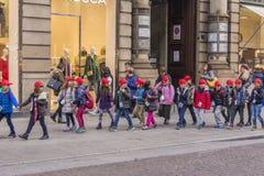 Milão, Itália 23-11-2017 Um grupo de estudantes mais novos que andam abaixo da rua no centro de Milão foto de stock