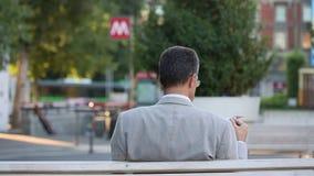 Milão - jornal da leitura do homem de negócios em um banco - estação de metro do metro de Cairoli no fundo vídeos de arquivo