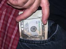 Mil dólares en un bolsillo Fotos de archivo libres de regalías