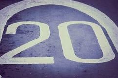 20 mil per timme undertecknar på en grov asfaltbeläggningväg Royaltyfri Bild
