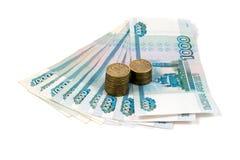 Mil rublos de billetes de banco y diez rublos de monedas aisladas en el fondo blanco Fotos de archivo libres de regalías