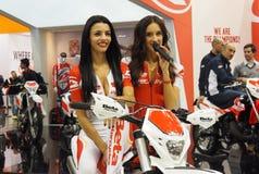 MILAAN, ITALIË - NOVEMBER 10: Twee modellen stelt op motorkruis bij EICMA, internationale motorfietstentoonstelling royalty-vrije stock foto