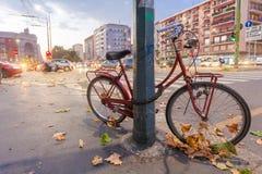 MILAAN, ITALIË - September 06, 2016: Rode gekleurde geparkeerd die fiets door slot aan de verlichting van de straatpool op de str Stock Foto