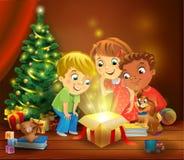 Milagro de la Navidad - niños que abren un regalo mágico al lado de un árbol de navidad stock de ilustración