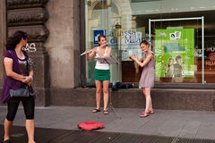 Two girls play the flute in the center of Milan Royalty Free Stock Photo