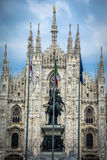 Milan cathedral exterior with Italian flagpoles and statue Stock Image