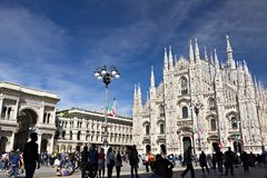 Milan Cathedral facade with flags on blue sky. The facade of the royalty free stock photo