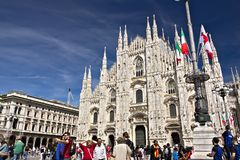 Milan Cathedral facade with flags on blue sky. The facade of the stock image