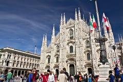 Milan Cathedral-voorgevel met vlaggen op blauwe hemel De voorgevel van stock afbeelding