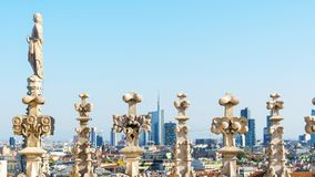 Milan cityscape through sculptures on the roof of Duomo cathedral. Milan city landscape from Duomo stock image